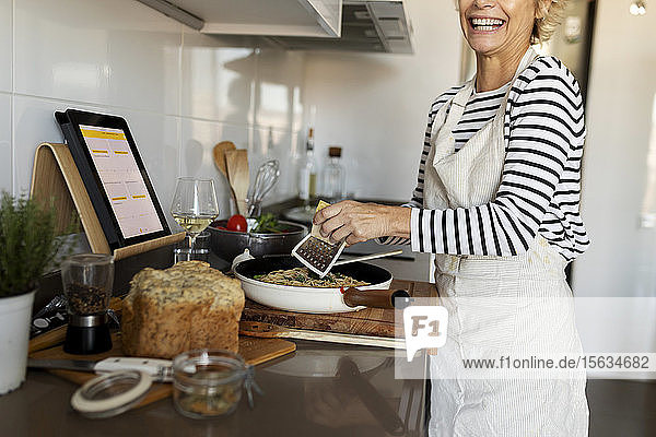 Happy mature woman with tablet cooking pasta dish in kitchen at home
