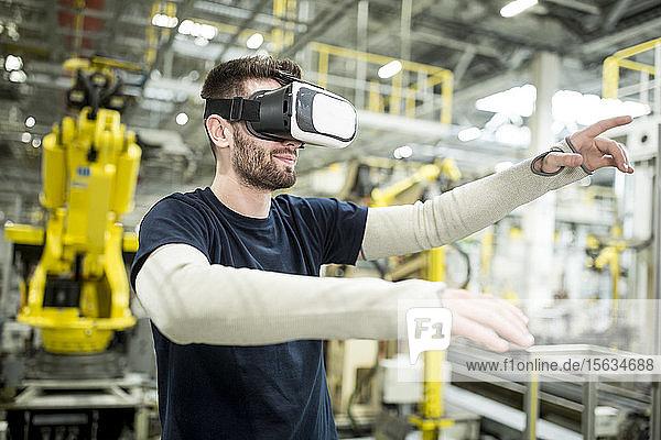 Mann mit VR-Brille in moderner Fabrik