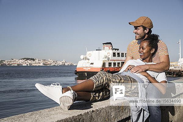 Glückliches junges Paar entspannt sich auf einer Mauer am Wasser  Lissabon  Portugal