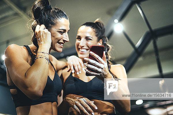 Lächelnde  gutaussehende weibliche Zwillinge mit Smartphone in einem Fitnessstudio