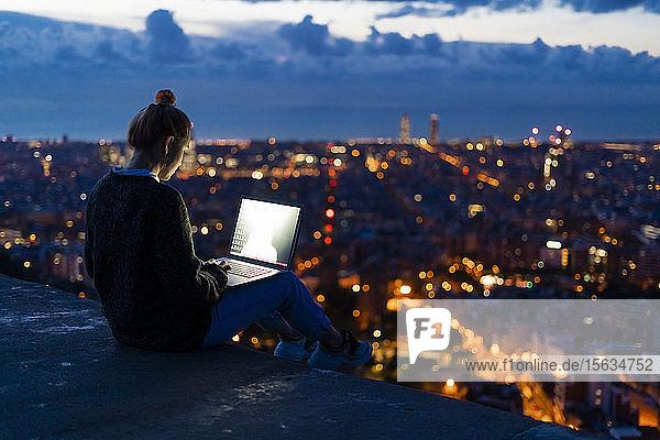 Junge Frau mit Laptop im Morgengrauen über der Stadt  Barcelona  Spanien