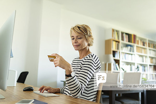 Mature woman using desktop pc for online shopping at home