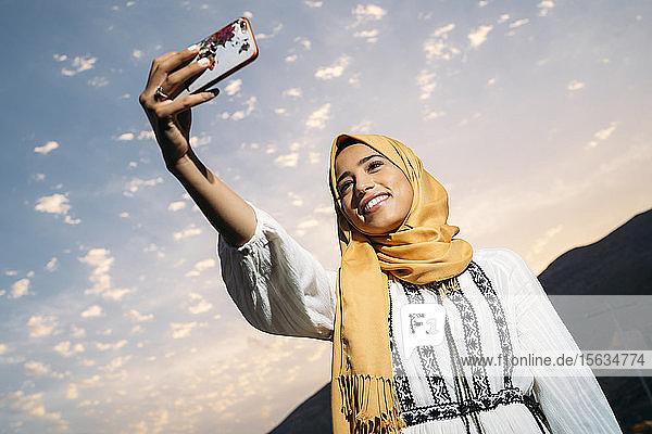 Junge muslimische Frau  die einen gelben Hidschab trägt  ein Smartphone benutzt und abends ein Selfie macht