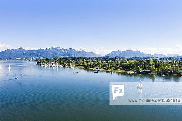 Deutschland  Bayern  Prien am Chiemsee  Segelboote fahren in Ufernähe des Chiemsees mit den Chiemgauer Alpen im Hintergrund
