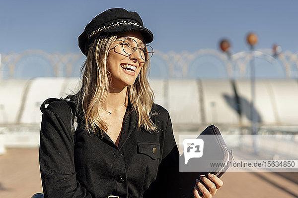 Junge blonde lachende Geschäftsfrau mit schwarzer Matrosenmütze und Laptoptasche in der Hand