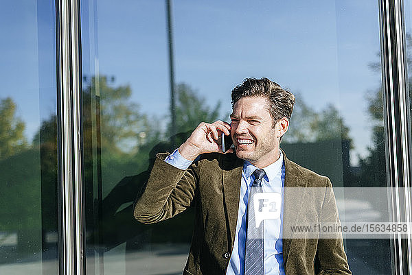 Happy businessman on the phone in urban business district  Madrid  Spain