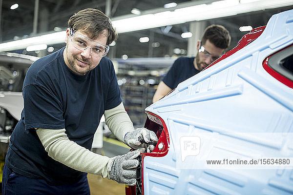Porträt eines selbstbewussten Mannes  der in einer modernen Autofabrik arbeitet