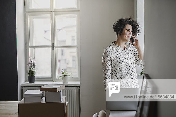 Young woman on the phone in home office looking out of window