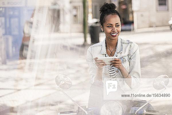 Lächelnde junge Frau mit Motorroller und Mobiltelefon in der Stadt  Lissabon  Portugal