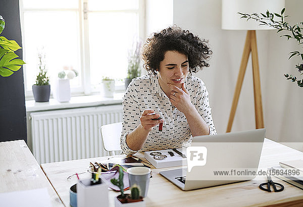 Smiling young woman working on laptop at desk