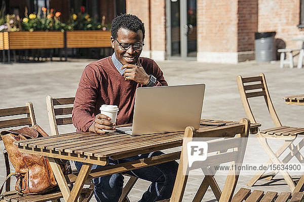 Young man using laptop in a coffee shop  drinking coffee