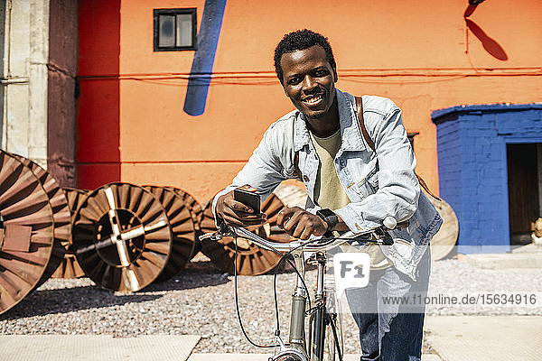 Relaxed young amn commuting in the city with hos bicycle  using smartphone