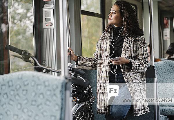 Junge Frau mit Kopfhörern  Smartphone und Fahrrad in der U-Bahn