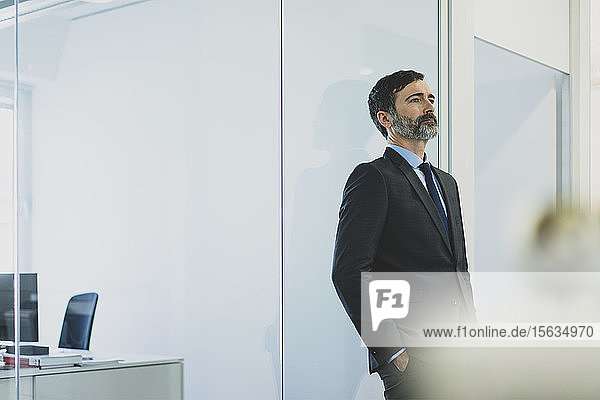 Thoughtful mature businessman leaning against glass wall in office