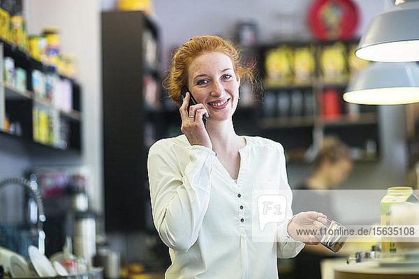 Junge Frau  die im Café arbeitet  telefoniert