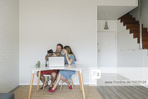 Lachende Frau und lachender Mann sitzen zusammen am Schreibtisch und schauen auf eine Digitalkamera