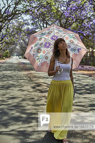 Frau geht mit ihrem Regenschirm auf einer Strasse  blühende Jacaranda-Bäume  Pretoria  Südafrika