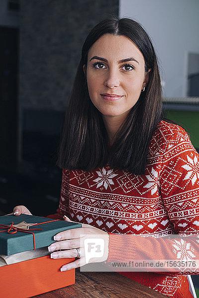 Porträt einer jungen Frau mit Weihnachtsgeschenk