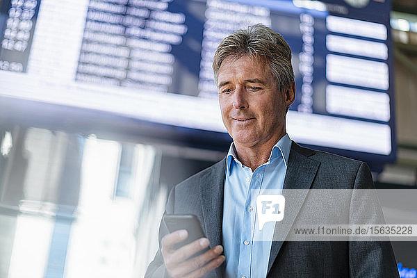 Älterer Geschäftsmann benutzt Mobiltelefon am Bahnhof