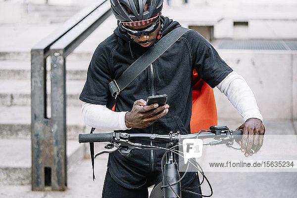 Stilvoller junger Mann mit Fahrrad  Smartphone und Kuriertasche in der Stadt