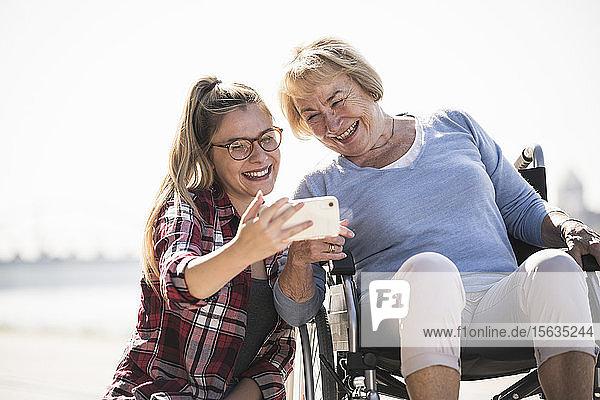 Junge Frau mit ihrer lächelnden Großmutter im Rollstuhl sitzend und mit einem Selfie