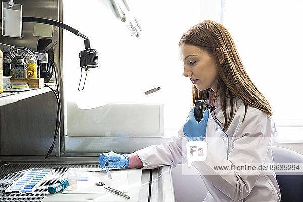 Frau untersucht Proben und zeichnet die Ergebnisse mit einem Diktiergerät auf  während sie in einem innovativen Labor arbeitet