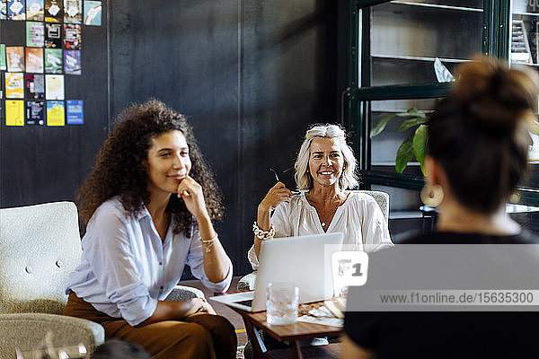 Businesswomen with laptop working together in loft office