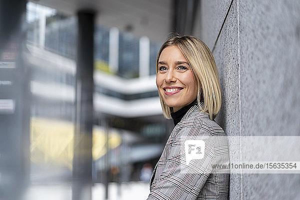 Porträt einer lächelnden jungen Geschäftsfrau  die an einer Wand lehnt