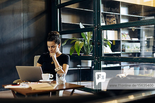 Casual young businesswoman using laptop in loft office