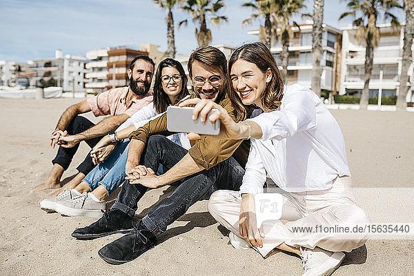 Glückliche Freunde sitzen am Strand und machen ein Selfie