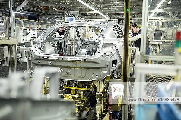 Zwei Kollegen arbeiten in einer modernen Autofabrik