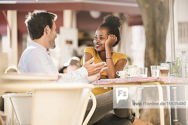 Glückliches junges Paar unterhält sich in einem Straßencafé