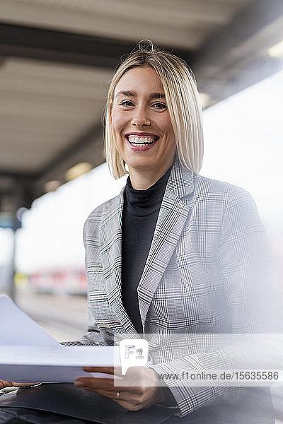 Porträt einer glücklichen jungen Geschäftsfrau mit Papieren am Bahnhof