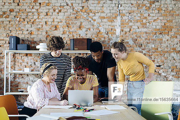 Young people working together at table using laptop