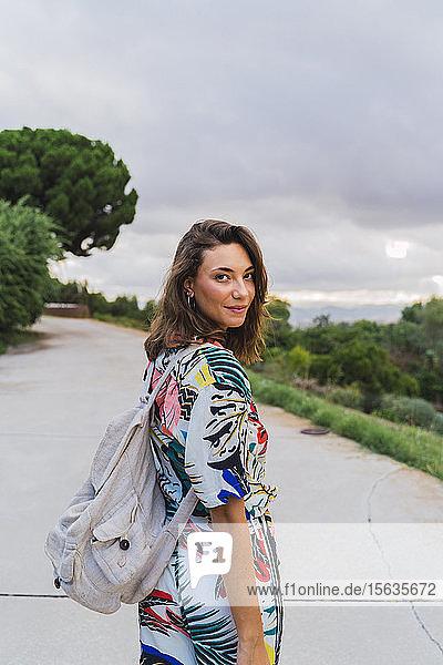 Porträt einer lächelnden jungen Frau mit Rucksack beim Spaziergang in einem Park