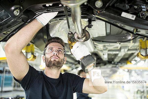 Mann arbeitet am Unterboden eines Autos in einer modernen Fabrik