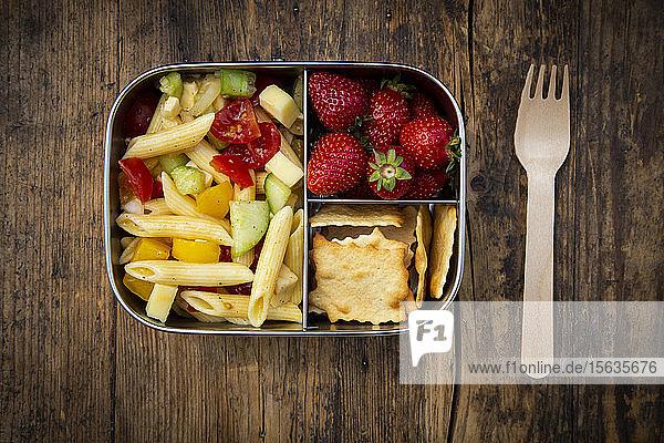 Direkt über Schuss Nudeln mit Erdbeeren und Crackern in Lunchbox auf Holztisch