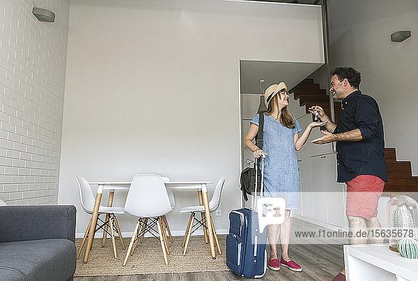 Tourist erhält vom Eigentümer den Schlüssel für ein modernes Ferienhaus