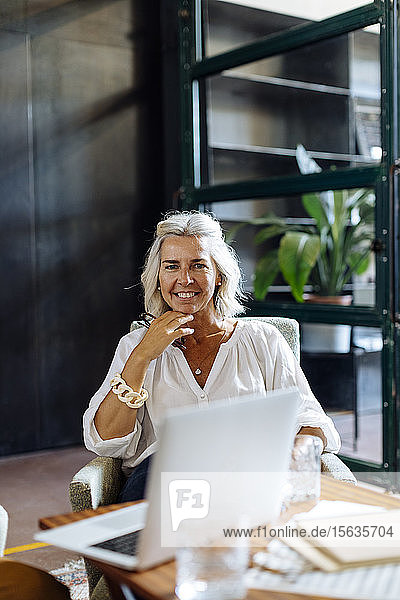Portrait of smiling mature businesswoman with laptop in loft office