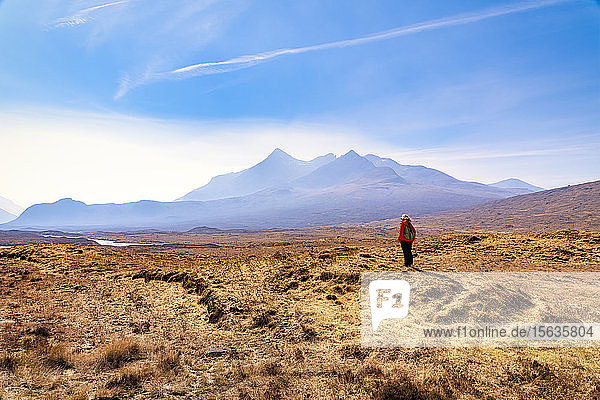 Mature woman standing on land while Cuillin mountains in background  Isle of Skye  Highlands  Scotland  UK