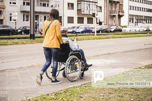 Back view of young woman pushing senior man with smartphone in wheelchair on pavement