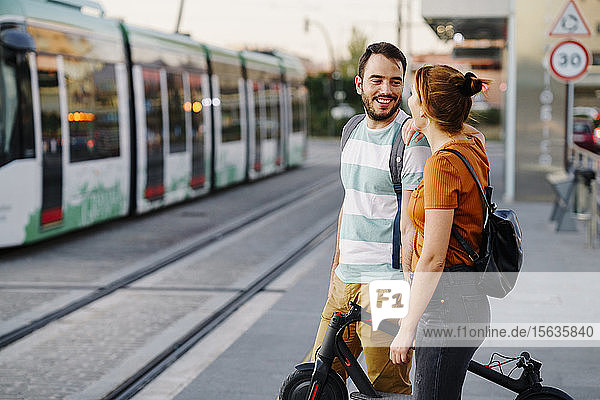 Couple with folded electric scooter waiting at tram stop