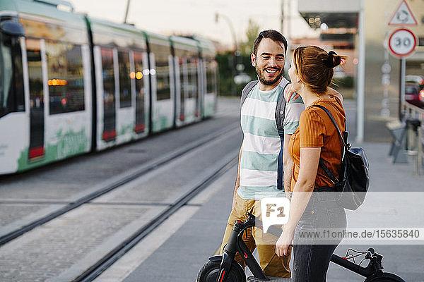 Ehepaar mit zusammengeklapptem Elektroroller wartet an der Straßenbahnhaltestelle