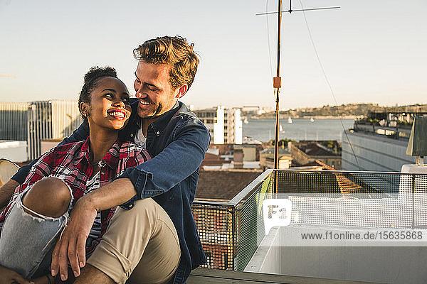 Glückliches  liebevolles junges Paar sitzt abends auf dem Dach Glückliches, liebevolles junges Paar sitzt abends auf dem Dach
