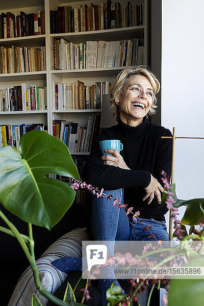 Happy mature woman drinking coffee and relaxing at home