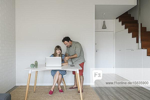 Paar mit Kreditkarte und Laptop in moderner Wohnung
