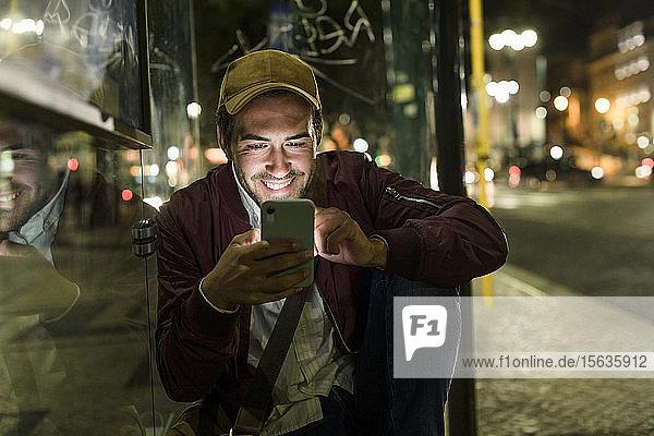 Porträt eines lächelnden jungen Mannes  der nachts an einer Bushaltestelle sitzt und sein Handy benutzt  Lissabon  Portugal