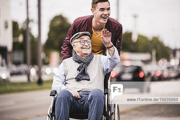 Portrait of laughing young man pushing happy senior man in wheelchair