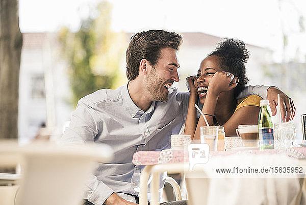 Lachendes junges Paar in einem Straßencafé