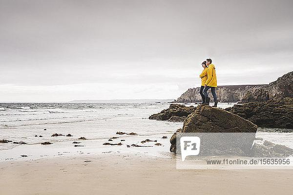 Junge Frau in gelben Regenjacken und auf einem Felsen am Strand stehend  Bretagne  Frankreich